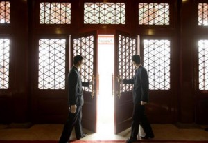 Waiters open a Chinese traditional red door inside a luxurious furniture museum in Beijing